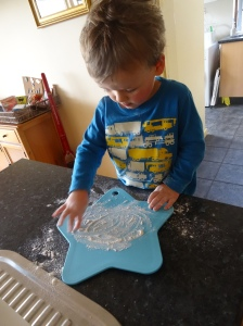 Drawing in flour while Mummy makes a loaf of bread